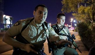 FILE - In this Oct. 1, 2017 file photo, police officers advise people to take cover near the scene of a shooting near the Mandalay Bay resort and casino on the Las Vegas Strip in Las Vegas. The Nevada Supreme Court has rejected a Las Vegas police bid to delay the release of records about the Oct. 1 mass shooting, including officer body camera videos, 911 recordings, evidence logs and written interview reports. Five of seven justices said Friday, April 27, 2018 the Las Vegas Metropolitan Police Department should make public the records that several media entities hope will shed light on the investigation of the deadliest mass shooting in modern U.S. history. (AP Photo/John Locher, File)