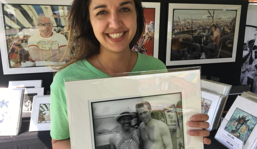 Amanda McFillen shows a picture taken at the 1989 New Orleans Jazz & Heritage Festival of saxophone player Charles Neville posing with Harry Connick Jr. The image was among those on sale Friday, April 27, 2018 at the festival by the Historic New Orleans Collection in New Orleans. Neville died Thursday, April 26, 2018. (AP Photo/Kevin McGill)
