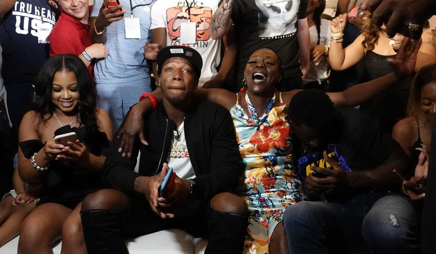 Alabama wide reciever Calvin Ridley; his mother, Kassna Daniels, right; and girlfriend, Dominique Fitchard, left, react as after he was picked by the Atlanta Falcons in the NFL football draft, at a watch party in Fort Lauderdale, Fla., Thursday, April 26, 2018. (Joe Cavaretta/South Florida Sun-Sentinel via AP)
