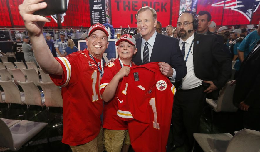 Kansas City Chiefs fans Chris Miller and his son Zane, 12, of Platte City, Mo., pose for a photo with Commissioner Roger Goodell during the first round of the NFL football draft, Thursday, April 26, 2018, in Arlington, Texas. (AP Photo/Michael Ainsworth)