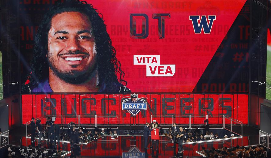 Commissioner Roger Goodell presents Washington's Vita Vea with his Tampa Bay Buccaneers jersey during the first round of the NFL football draft, Thursday, April 26, 2018, in Arlington, Texas. (AP Photo/David J. Phillip)