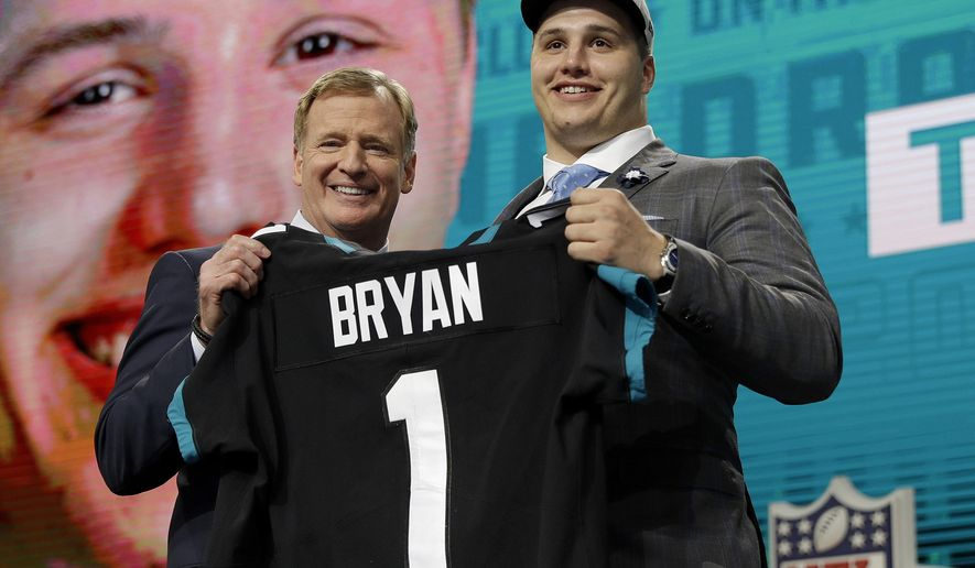 Commissioner Roger Goodell presents Florida's Taven Bryan with his Jacksonville Jaguars team jersey during the first round of the NFL football draft, Thursday, April 26, 2018, in Arlington, Texas. (AP Photo/David J. Phillip)