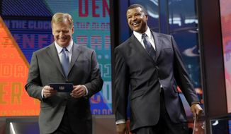 NFL Commissioner Roger Goodell and former player Stephen Atwater walk off the stage after announcing SMU's Courtland Sutton as the Denver Broncos pick during the second round of the NFL football draft, Friday, April 27, 2018, in Arlington, Texas. (AP Photo/Eric Gay)