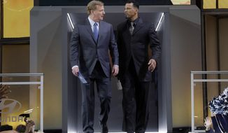 NFL Commissioner Roger Goodell, left, and former Pittsburgh Steelers player Rod Woodson walk onto the stage to announce Oklahoma State's James Washington as the Steelers' selection during the second round of the NFL football draft Friday, April 27, 2018, in Arlington, Texas. (AP Photo/Eric Gay)