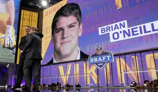 Former Minnesota Vikings player Keith Millard, left, embraces NFL Commissioner Roger Goodell after announcing Pittsburgh's Brian O'Neill as the Vikings' selection during the second round of the NFL football draft Friday, April 27, 2018, in Arlington, Texas. (AP Photo/Eric Gay)