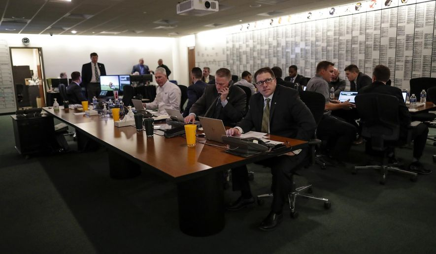In a photo provided by the Green Bay Packers, team coaches and officials work in the draft room at Lambeau Field on Thursday, April 26, 2018, in Green Bay, Wis. (Evan Siegle/Green Bay Packers via AP)