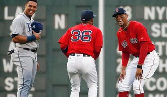 Boston Red Sox's Xander Bogaerts, right, jokes with teammate Eduardo Nunez (36) and Tampa Bay Rays' Carlos Gomez before a baseball game in Boston, Friday, April 27, 2018. (AP Photo/Michael Dwyer)