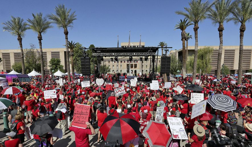Teachers rally outside the Capitol, Friday, April 27, 2018, in Phoenix, on their second day of walkouts. Teachers in Arizona and Colorado walked out of their classes over low salaries keeping hundreds of thousands of students out of school. It's the latest in a series of strikes across the nation over low teacher pay. (AP Photo/Matt York)