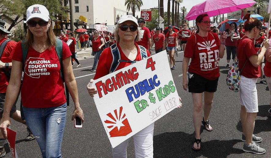 Thousands march to the Arizona Capitol for higher teacher pay and public school funding on the first day of a state-wide teachers strike Thursday, April 26, 2018, in Phoenix. Arizona leaders dealing with an unprecedented teacher strike are paying the political price for long-festering resentment among many public school teachers. (AP Photo/Ross D. Franklin)