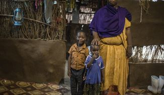 In this April 16, 2018 photo, Saido Muhina Khamis stands in her home with her children, Ibrahim Muhamed, 6, left, and his sister, Shukri, 3, at the Kakuma Refugee Camp in Kakuma, Kenya. Khamis thought she'd be in the United States by now, starting a new life with her mother and her own family, but instead, the Somali woman is still at the camp, where she has been since 2009. (International Rescue Committee/Kellie Ryan via AP)