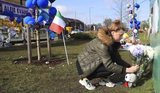 A woman leaves flowers outside Alder Hey Children's Hospital in Liverpool, England, following the death of 23-month-old, Alfie Evans, Saturday April 28, 2018. Alfie Evans, the sick British toddler whose parents won support from Pope Francis during a protracted legal battle over his treatment, died early Saturday. He was 23 months old. (Peter Byrne/PA via AP)