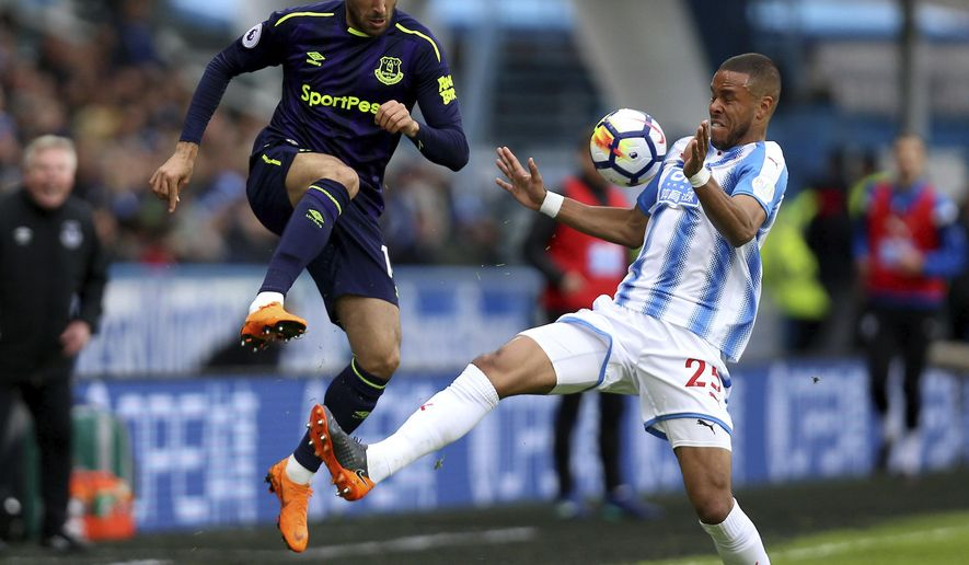 Huddersfield Town's Mathias Jorgensen, right, attempts to keep the ball from Everton's Cenk Tosun, during their English Premier League soccer match at the John Smith's Stadium in Huddersfield, England, date: Saturday April 28, 2018. (Nigel French/PA via AP)