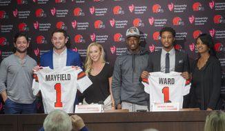 Cleveland Browns first-round pick Baker Mayfield, second from left, stands with his brother Matt Mayfield, left, and girlfriend, Emily Wilkinson along with fellow first-round pick Denzel Ward, second from right, with his brother Paul Ward III and his mother, Nicole Ward, far right, after a news conference at the Browns headquarters in Berea, Ohio, Friday, April 27, 2018. Mayfield was the first selection in the draft, Ward the fourth. (AP Photo/Phil Long)