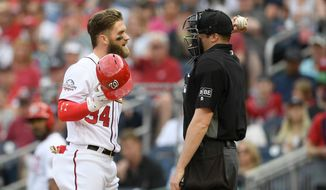 Washington Nationals' Bryce Harper (34) talks with home plate umpire Nic Lentz, right, after he was called out on strikes during the third inning of a baseball game against the Arizona Diamondbacks, Saturday, April 28, 2018, in Washington. (AP Photo/Nick Wass)