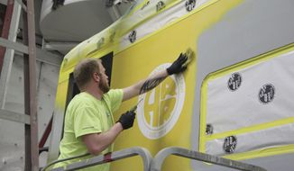 In this April 13, 2018 photo, Joseph Freel puts the finishing touches on the Alaska Railroad Corp. logo at Alaska Industrial Paint in Anchorage, Alaska. The Alaska Railroad used to ship some of its 45 passenger cars on barges to Seattle every year, then put them back on tracks for a long chug to the Midwest for repairs and paint jobs. The costs piled up, according to Tim Sullivan, the Alaska Railroad Corp. director of external affairs. Not only did it cost money for the shipping and the work. There was a price for flights and hotels for officials to inspect the work as well. (Naomi Klouda/Alaska Journal of Commerce via AP)