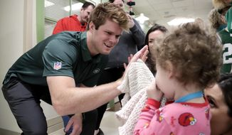 New York Jets quarterback Sam Darnold, left, who was drafted No. 3 overall in Thursday's NFL football draft, gives a high five to Sydney Kaplan, 3, of Mahwah, N.J., during a visit to the Goryeb Children's Hospital, Saturday, April 28, 2018, in Morristown, N.J. (AP Photo/Julio Cortez)