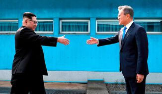 FILE - In this April 27, 2018 file photo, North Korean leader Kim Jong Un, left, prepares to shake hands with South Korean President Moon Jae-in over the military demarcation line at the border village of Panmunjom in Demilitarized Zone. Despite its feel-good emphasis on relationship-building, the first inter-Korean summit in more than a decade left a lot of question marks around the biggest and most contentious agenda item of them all: denuclearization. And that puts the ball squarely in the court of President Donald Trump, whose much anticipated sit-down with Kim is expected to be just weeks away. (Korea Summit Press Pool via AP, File)