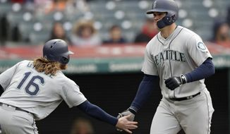 Seattle Mariners' Ryon Healy, right, is congratulated by Ben Gamel after Healy hit a two-run home run off Cleveland Indians relief pitcher Dan Otero during the ninth inning of a baseball game, Saturday, April 28, 2018, in Cleveland. Gamel scored on the homer. The Mariners won 12-4. (AP Photo/Tony Dejak)