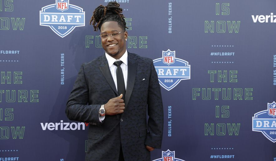 Central Florida's Shaquem Griffin poses for photos on the red carpet before the first round of the NFL football draft, Thursday, April 26, 2018, in Arlington, Texas. (AP Photo/Eric Gay)