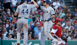 Tampa Bay Rays' Wilson Ramos, center, celebrates his two-run home run with C.J. Cron (44) as Boston Red Sox's Christian Vazquez kneels behind home plate during the third inning of a baseball game in Boston, Saturday, April 28, 2018. (AP Photo/Michael Dwyer)