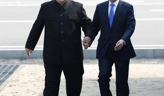In this Friday, April 27, 2018, file photo, North Korean leader Kim Jong Un, left, and South Korean President Moon Jae-in cross the military demarcation line to the South side at the border village of Panmunjom in the Demilitarized Zone. Kim made history Friday by crossing over the world's most heavily armed border to greet his rival, Moon, for talks on North Korea's nuclear weapons. (Korea Summit Press Pool via AP, File)