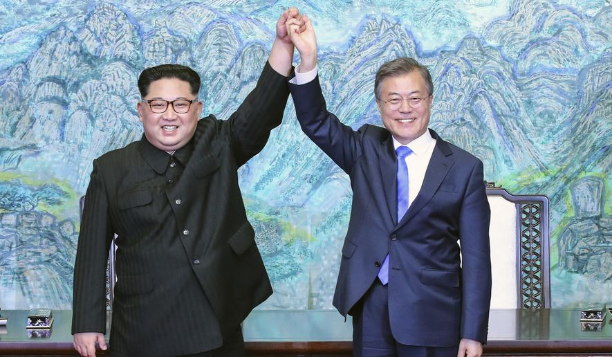 North Korean leader Kim Jong Un, left, and South Korean President Moon Jae-in raise their hands after signing a joint statement at the border village of Panmunjom in the Demilitarized Zone, South Korea, Friday, April 27, 2018. (Korea Summit Press Pool via AP)