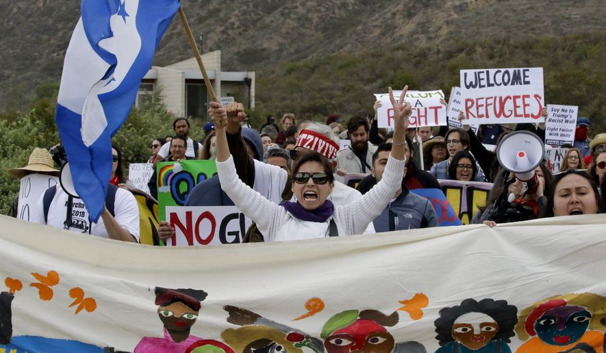 Demonstrators march to meet Central American migrants traveling in a caravan for a gathering at the border on the beach where the border wall ends in the ocean, Sunday, April 29, 2018, in San Diego. (AP Photo/Chris Carlson)