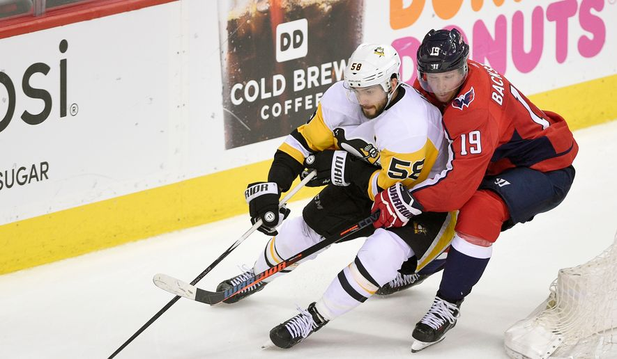 Washington Capitals center Nicklas Backstrom (19), of Sweden, holds onto Pittsburgh Penguins defenseman Kris Letang (58) during the third period in Game 2 of an NHL second-round hockey playoff series, Sunday, April 29, 2018, in Washington. (AP Photo/Nick Wass) ** FILE **
