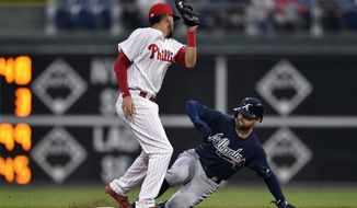 Atlanta Braves' Ender Inciarte, right, slides safely past Philadelphia Phillies' J.P. Crawford to steal second base during the first inning of a baseball game, Friday, April 27, 2018, in Philadelphia. (AP Photo/Derik Hamilton)