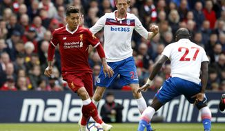Liverpool's Roberto Firmino, left, and Stoke City's Badou Ndiaye, right, face off with Peter Crouch behind, during the English Premier League soccer match at Anfield in Liverpool, England, Saturday April 28, 2018. (Martin Rickett/PA via AP)