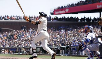 San Francisco Giants' Evan Longoria, center, follows through on his three-run home run against the Los Angeles Dodgers during the first inning of a baseball game Sunday, April 29, 2018, in San Francisco. (AP Photo/Marcio Jose Sanchez)
