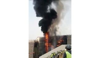 In this image made from a video provided by Almanassa people watch as smoke rises from a fire at the new Grand Egyptian Museum, located near the famed pyramids of Giza just outside Cairo. The museum covers about 490,000 square meters (586,120 square yards) and will house some of Egypt's most unique and precious artifacts, including many belonging to the famed boy King Tutankhamun. Egyptian officials said that the fire caused no significant damage or injuries. (Almanassa via AP)