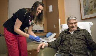 Christina Gay, left, administers medication to Gene Wickstrom of Cathlamet during her April 5, 2018, night shift at Legacy Salmon Creek Medical Center in Vancouver, Wash. Gay's class at Hough Elementary School was tapped for the local I Have a Dream program in 1997 and she studied nursing at Clark College and Washington State University Vancouver. (AP/Alisha Jucevic/The Columbian via AP)