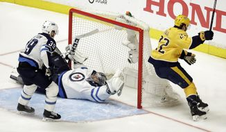 Nashville Predators left wing Kevin Fiala (22), of Switzerland, scores the winning goal against Winnipeg Jets goalie Connor Hellebuyck during the second overtime in Game 2 of an NHL hockey second-round playoff series Sunday, April 29, 2018, in Nashville, Tenn. The Predators won 5-4 to tie the series 1-1. Also defending is Jets' Toby Enstrom (39). (AP Photo/Mark Humphrey)