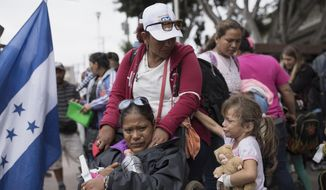 Members of a Central American family traveling with a caravan of migrants prepare to cross the border and apply for asylum in the United States, in Tijuana, Mexico, Sunday, April 29, 2018. A group of Central Americans who journeyed in a caravan to the U.S. border resolved to turn themselves in and ask for asylum Sunday in a direct challenge to the Trump administration - only to have U.S. immigration officials announce that the San Diego crossing was already at capacity. (AP Photo/Hans-Maximo Musielik)