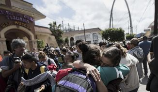 Central Americans who travel with a caravan of migrants embrace in Tijuana, Mexico, before crossing the border and request asylum in the United States, Sunday, April 29, 2018. A group of Central Americans who journeyed in a caravan to the U.S. border resolved to turn themselves in and ask for asylum Sunday in a direct challenge to the Trump administration - only to have U.S. immigration officials announce that the San Diego crossing was already at capacity. (AP Photo/Hans-Maximo Musielik)