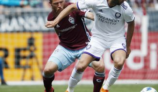 Colorado Rapids midfielder Enzo Martinez, left, battles for control of the ball with Orlando City forward Justin Meram in the first half of an MLS soccer match Sunday, April 29, 2018, in Commerce City, Colo. (AP Photo/David Zalubowski)