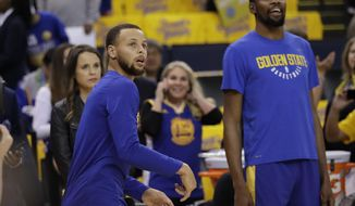 Golden State Warriors' Stephen Curry, left, watches his shot next to teammate Kevin Durant as players warm up for Game 1 of an NBA basketball second-round playoff series against the New Orleans Pelicans,Saturday, April 28, 2018, in Oakland, Calif. (AP Photo/Marcio Jose Sanchez)