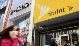 In this April 27, 2010, file photo, a woman using a cell phone walks past T-Mobile and Sprint stores in New York. T-Mobile and Sprint are trying again to combine in a deal that would reshape the U.S. wireless landscape, the companies announced Sunday, April 29, 2018. (AP Photo/Mark Lennihan, File)