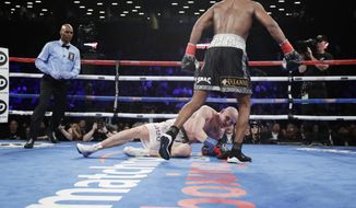Daniel Jacobs walks away from Poland's Maciej Sulecki after knocking him down during the 12th round of a middleweight boxing match early Sunday, April 29, 2018, in New York. Jacobs won the fight. (AP Photo/Frank Franklin II)