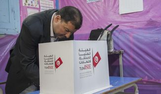 A Tunisian policeman dressed in civilian clothing casts his vote during municipal elections at a polling station for the police and military in Tunis, Sunday, April 29, 2018. This is the first time in Tunisian history that the military and police participate in the voting for the municipal elections, which also the first to be held in the country since the 2011 revolution. (AP Photo/Hassene Dridi)
