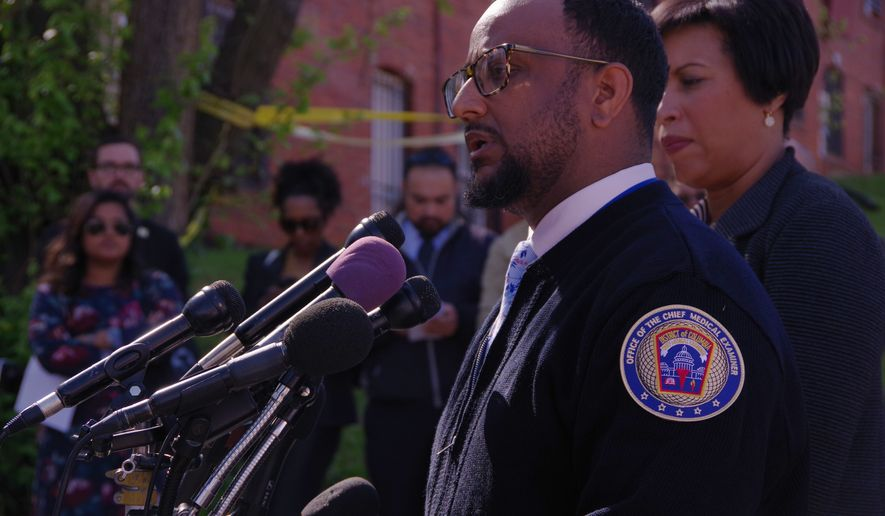 Photo by Julia Airey / The Washington Times      Dr. Roger A. Mitchell Jr., chief medical officer for the District, addresses a press conference Monday, April 30, on the discovery of skeletal remains of three women in Southeast. Flanking Dr. Mitchell is D.C. Mayor Muriel Bowser.