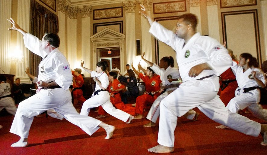 Rep. Nick Smith, R-Mich., left, and Rep. Jessie Jackson Jr. D-Il.,  warm-up before taking part in the congressional Tae Kwon Do Black Belt examination presented by Grand Master Jhoon Rhee Monday, July 23, 2001 on Capital Hill in Washington. (AP Photo/Pablo Martinez Monsivais)