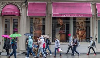 In this April 4, 2018, file photo, shoppers walk past the Victoria's Secret store on Broadway in the Soho neighborhood of New York. On Monday, April 30, the Commerce Department issues its March report on consumer spending. (AP Photo/Mary Altaffer, File)