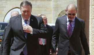 U.S. Secretary of State Mike Pompeo, left, is greeted by Jordan's Foreign Minister Ayman Safadi, right, before his meeting with Jordan's King Abdullah II, in Amman, Jordan, Monday April 30, 2018.  Pompeo said Monday that a resolution to the Israeli-Palestinian conflict remains a priority for the Trump administration. (Khalil Mazraawi/Pool via AP)