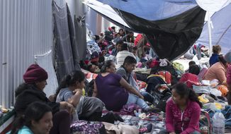 People who traveled with the annual caravan of Central American migrants, rest where the group set up camp to wait for access to request asylum in the U.S., outside the El Chaparral port of entry building at the US-Mexico border in Tijuana, Mexico, Monday, April 30, 2018. About 200 people in a caravan of Central American asylum seekers waited on the Mexican border with San Diego for a second straight day on Monday to turn themselves in to U.S. border inspectors, who said the nation's busiest crossing facility did not have enough space to accommodate them. (AP Photo/Hans-Maximo Musielik)