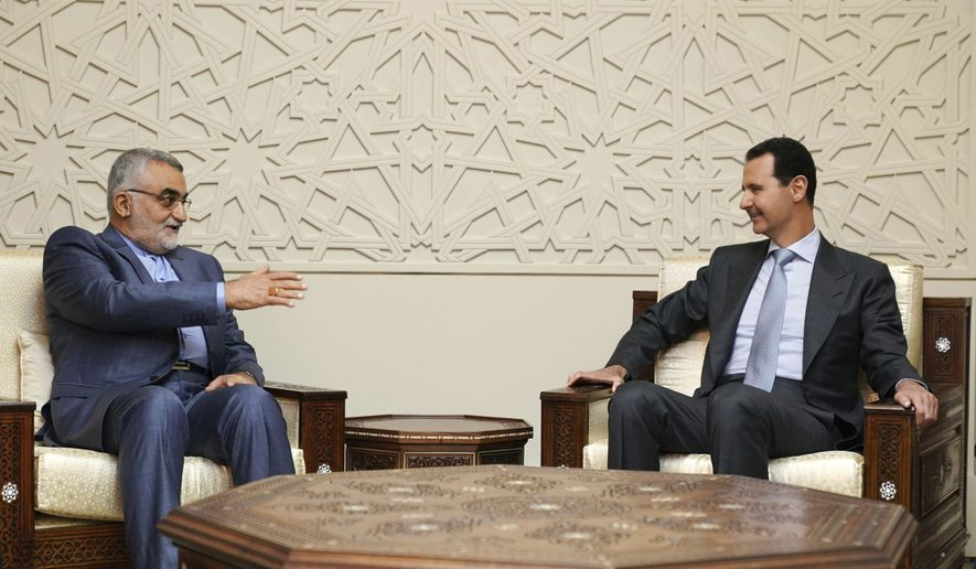 In this photo released by the Syrian official news agency SANA, Syrian President Bashar Assad, right, meets with Alaeddin Boroujerdi, left, the head of Iran's parliamentary committee on national security and foreign policy, in Damascus, Syria, Monday, April 30, 2018. The meeting came as a missile attack targeting government outposts in Syria's northern region killed at least 26 pro-government fighters, mostly Iranians, amid soaring Mideast tensions. (SANA via AP)