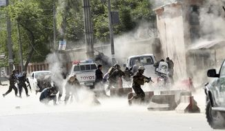 Security forces run from the site of a suicide attack after the second bombing in Kabul, Afghanistan, Monday, April 30, 2018. A coordinated double suicide bombing hit central Kabul on Monday morning, (AP Photo/Massoud Hossaini)