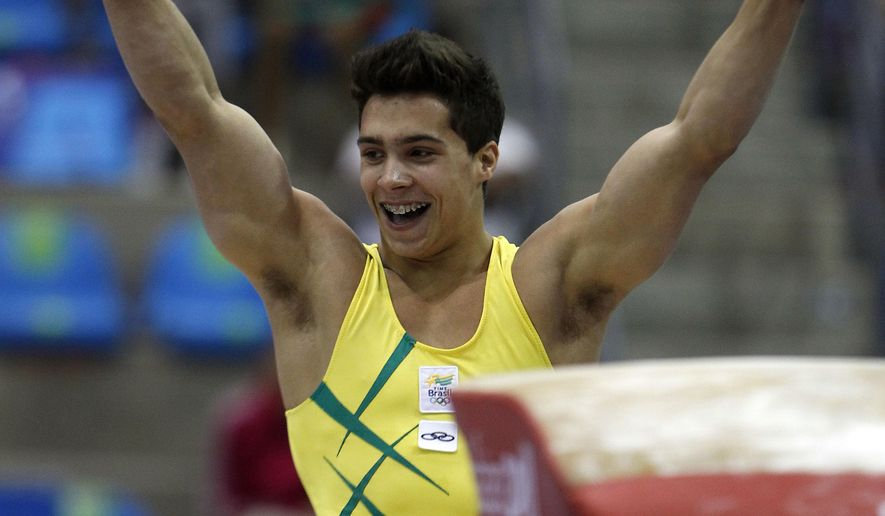 """FILE - In this Oct. 25, 2011 file photo, Brazil's Petrix Barbosa celebrates after competing on the vault at the men's artistic gymnastics team qualifications and finals of the Pan American Games in Guadalajara, Mexico. A community center has fired on Monday, April 20, 2018, a former coach of the Brazilian national gymnastics team after a news report revealed that dozens of athletes he worked with have accused him of sexual abuse. One of those, Petrix Barbosa, said the abuse started when he was 10 or 11. """"I woke up with him, I don't know how many times, with his hand down my pants,"""" said Barbosa, who was a gold medalist at the Pan American Games in 2011. (AP Photo/Dario Lopez-Mills, File)"""