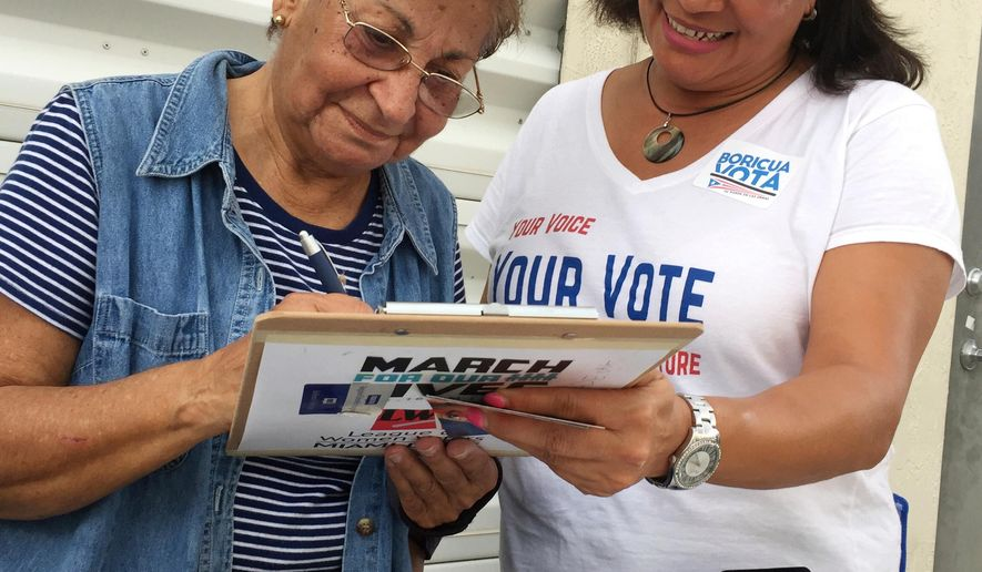 "In this April 8, 2018 photo, Marisol Zenteno, right, from The League of Women Voters, registering Aida Merced Lopez, who moved to Miami from Puerto Rico in April 2017, during a festival in Kendall, Florida. ""We are just working so the Puerto Rican community can have its voice heard,"" said volunteer Zenteno as she took a break from working a line of people waiting to buy pork and rice. ""They have the right when they come here to vote."" (AP Photo/Gisela Salomon)"